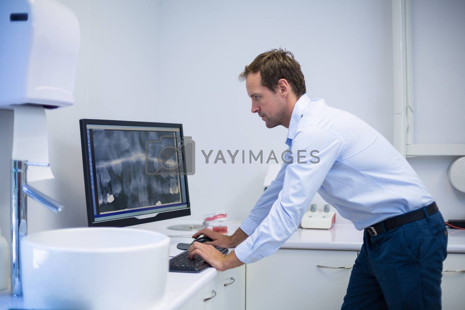 Attentive dentist examining an x-ray on computer in dental clinic