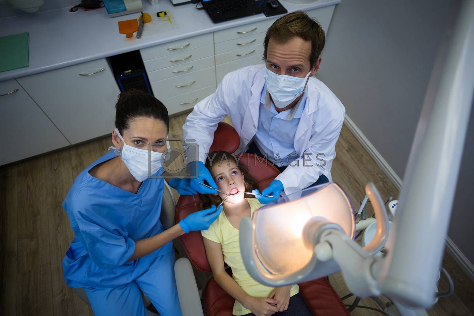 Portrait of dentists examining a young patient with tools in dental clinic
