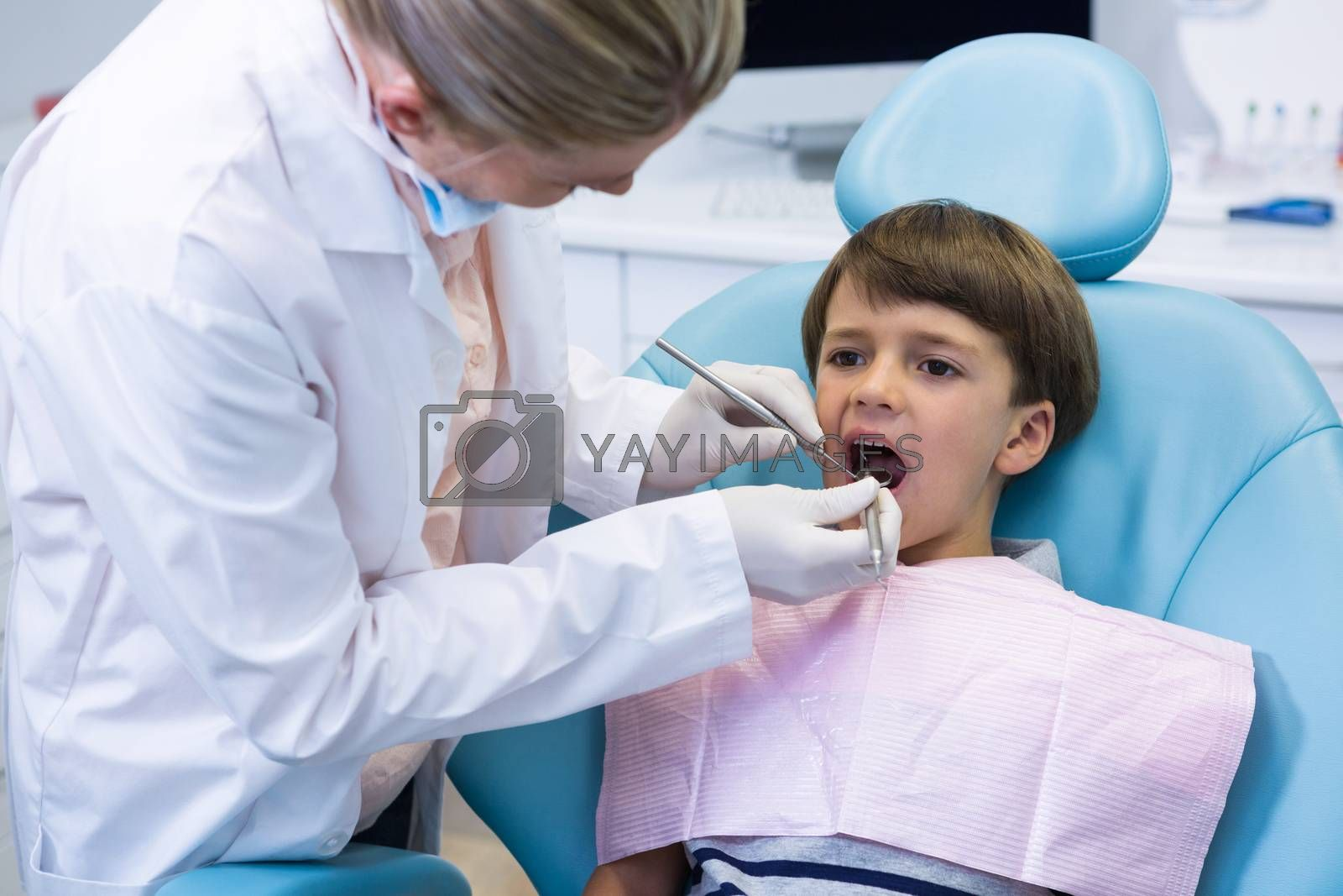 Boy receiving dental treatment by dentist at medical clinic