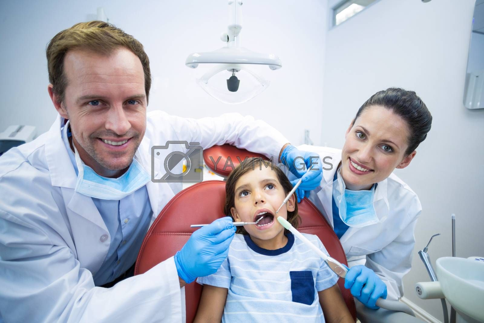 Portrait of dentists examining young patient in dental clinic