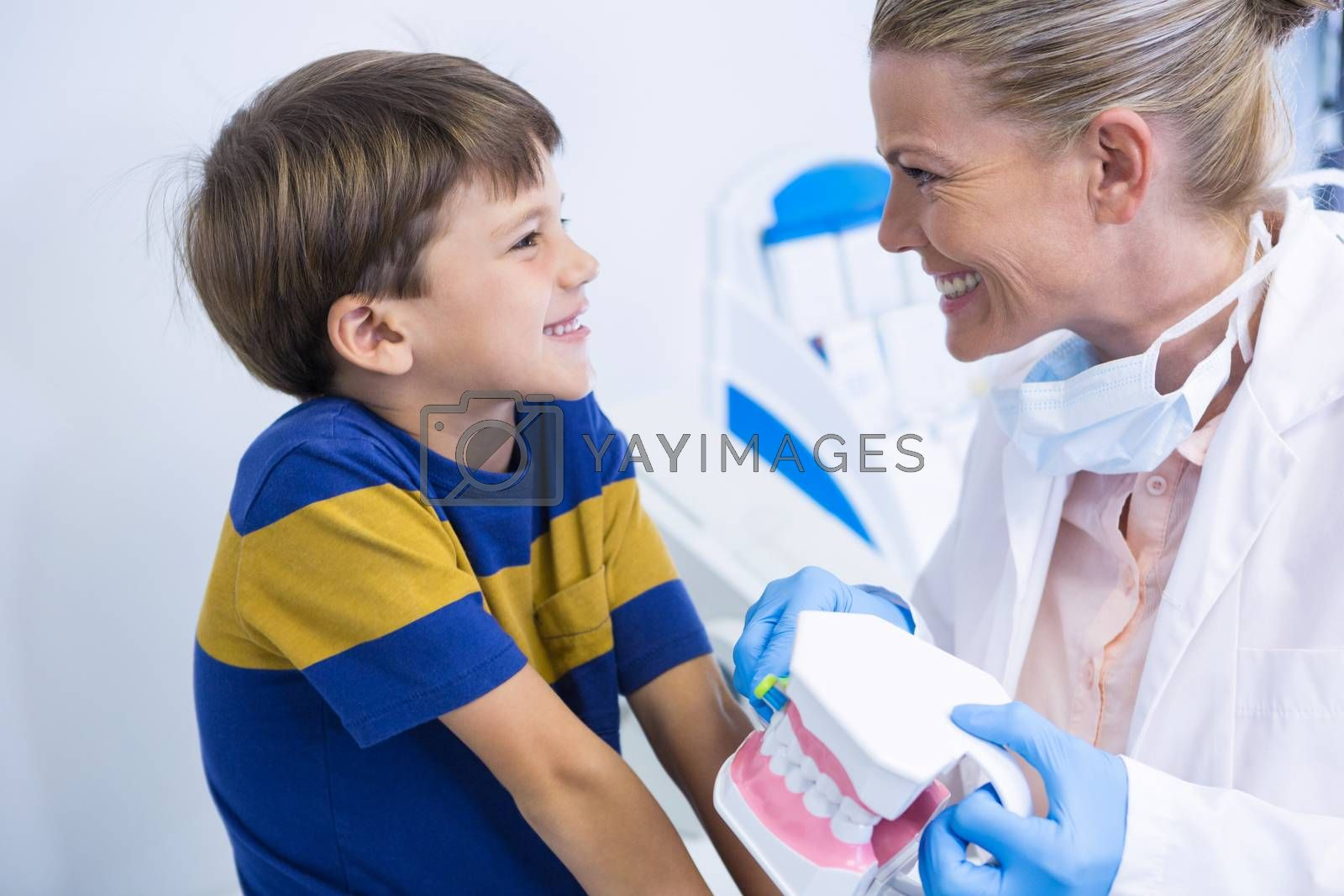 Happy dentist holding dental mold while looking at boy in clinic