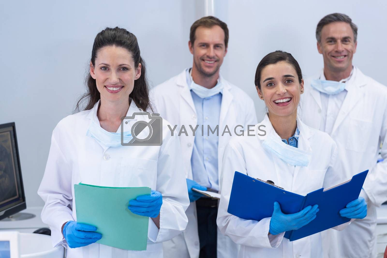 Portrait of smiling dentists standing in dental clinic