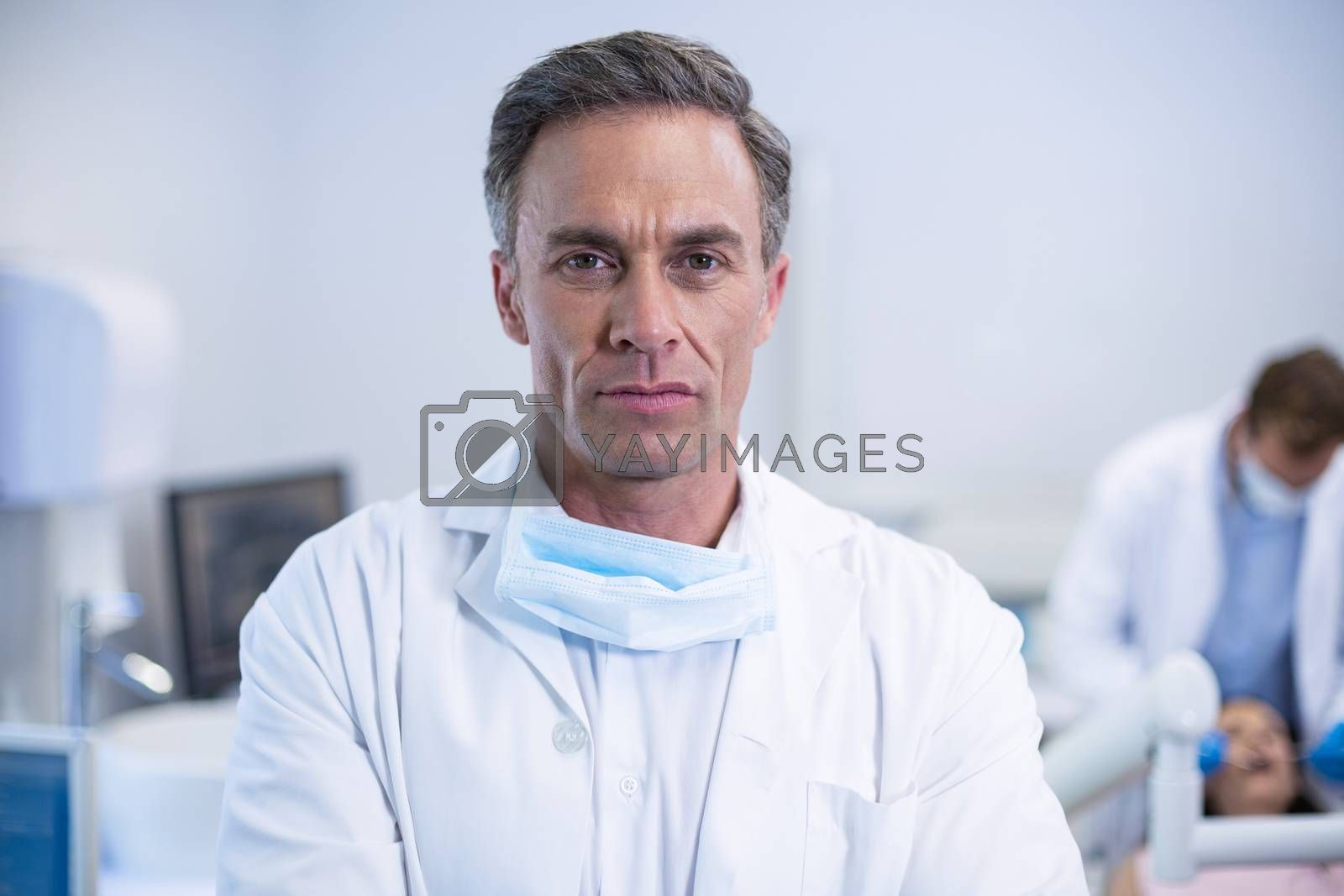 Portrait of confident dentist standing at dental clinic