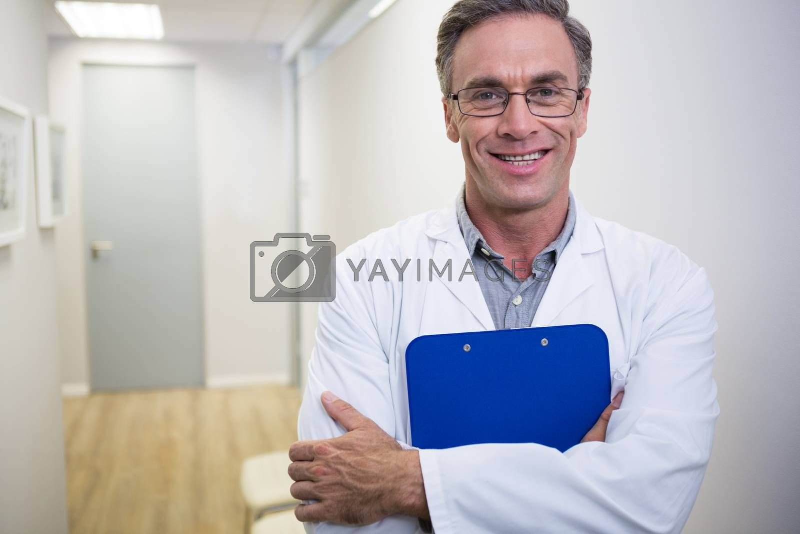 Portrait of smiling dentist holding file while standing at lobby in dental clinic
