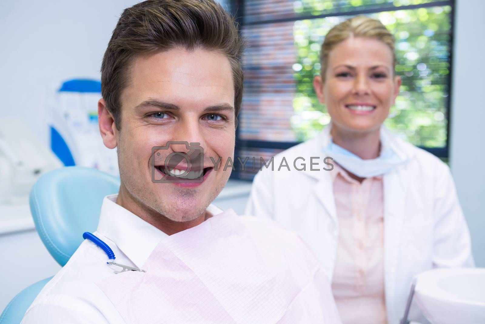 Portrait of smiling man and dentist sitting at dental clinic