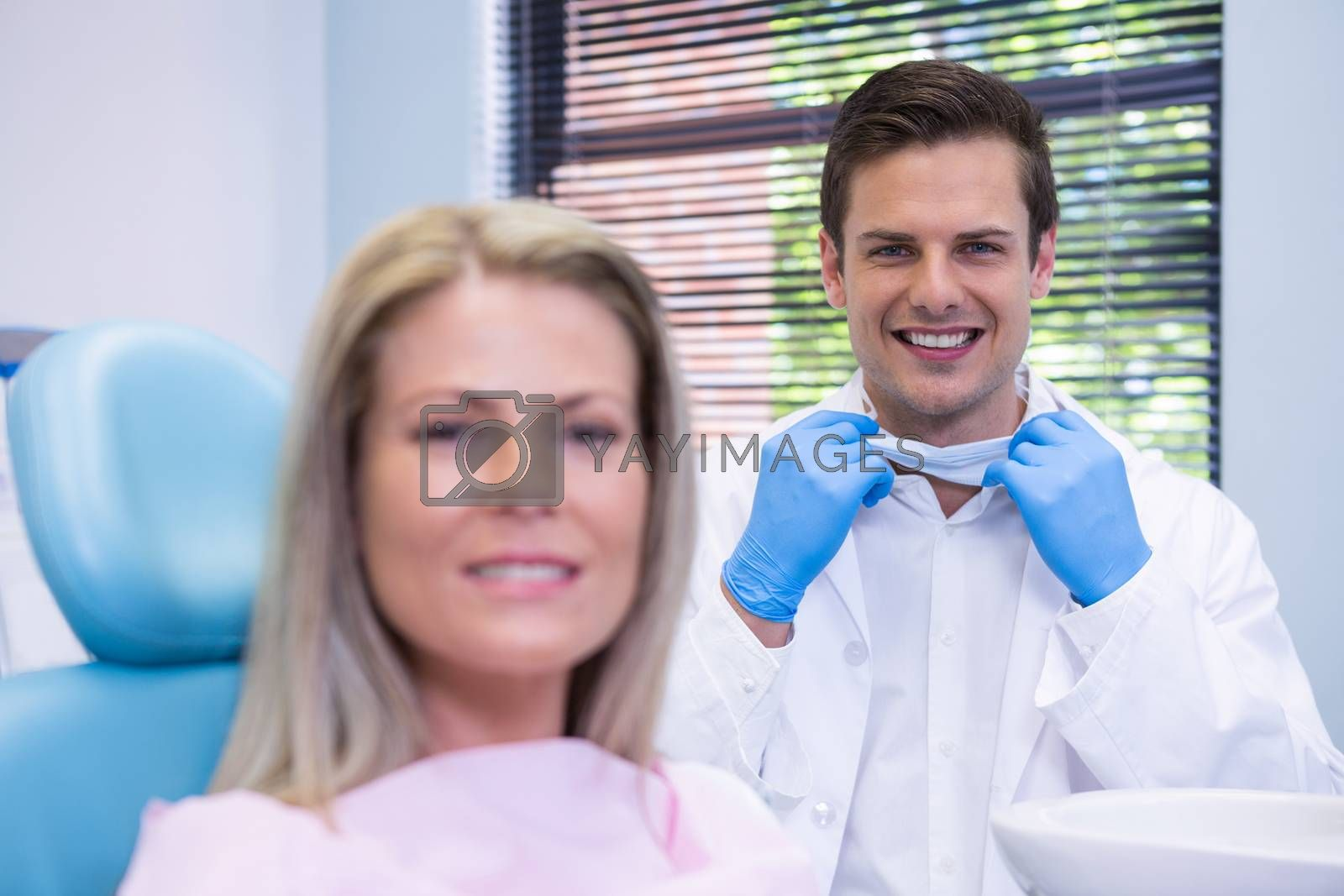 Portrait of happy patient and dentist  at dental clinic