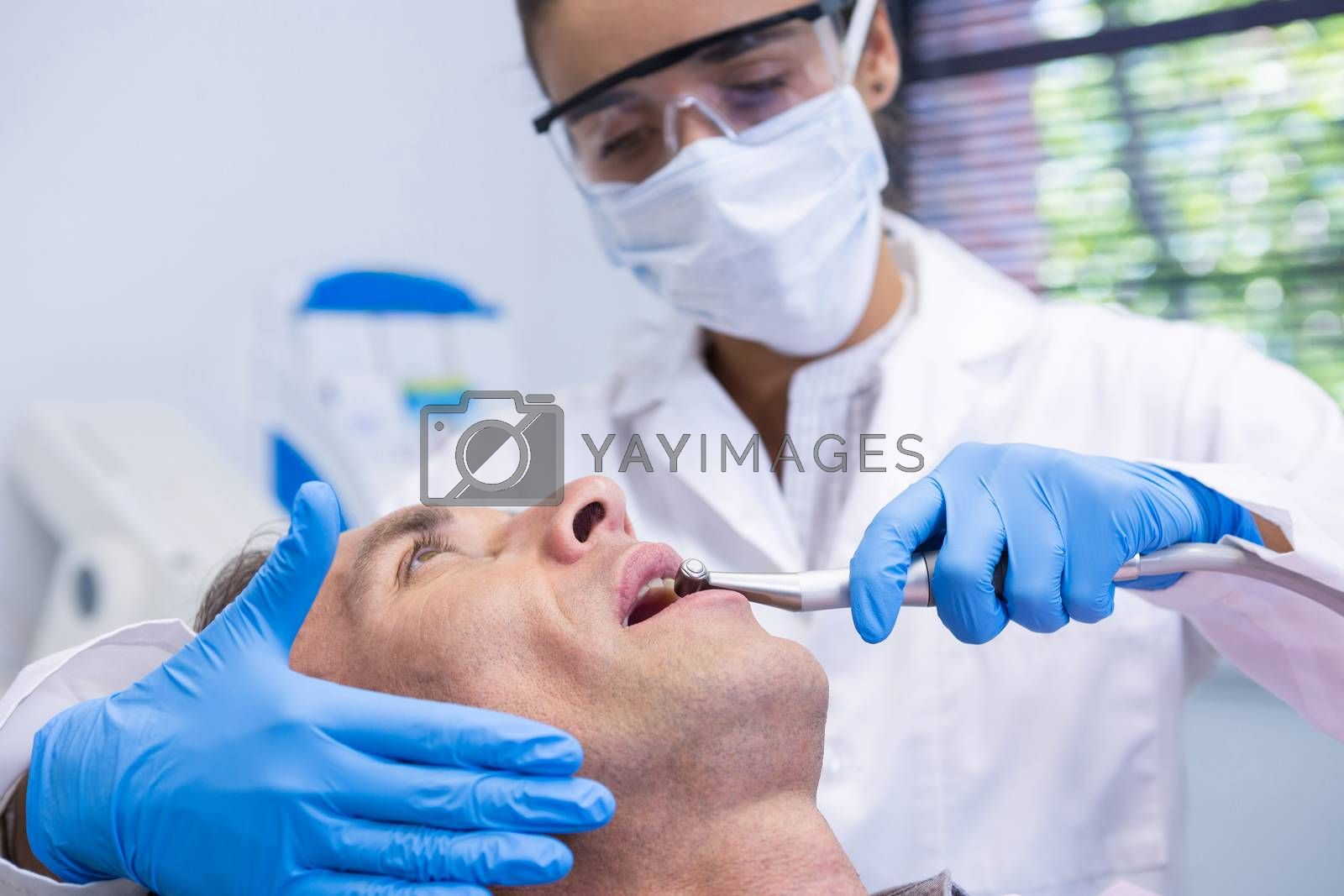 Close up of man receiving dental treatment by dentist at clinic