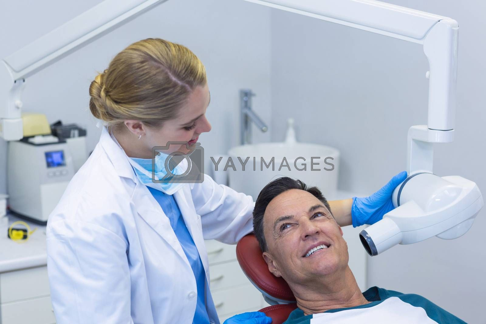Dentist examining a male patient with dental tool in clinic