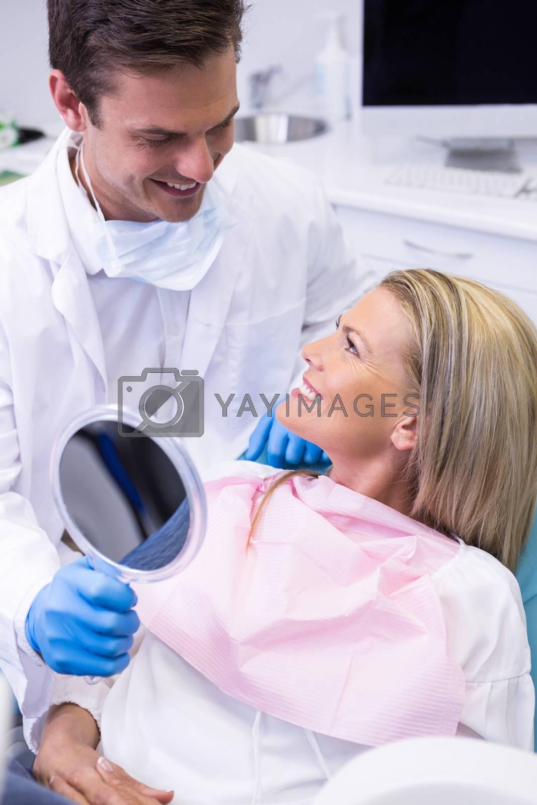 Dentist showing mirror to happy patient by Wavebreakmedia
