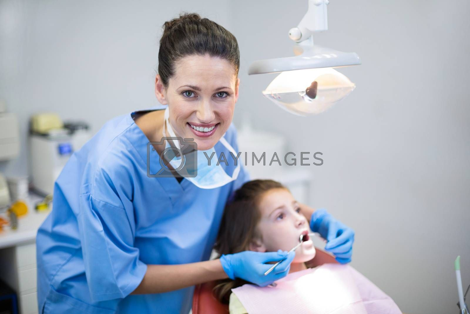 Portrait of dentist examining a young patient with tools in dental clinic