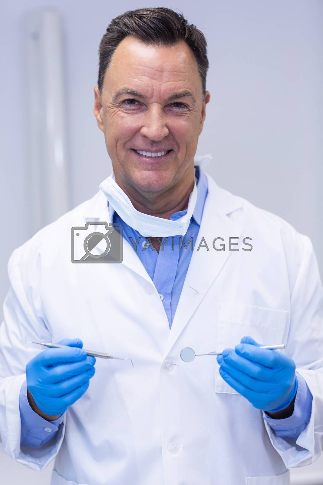 Portrait of smiling dentist holding dental tools at dental clinic