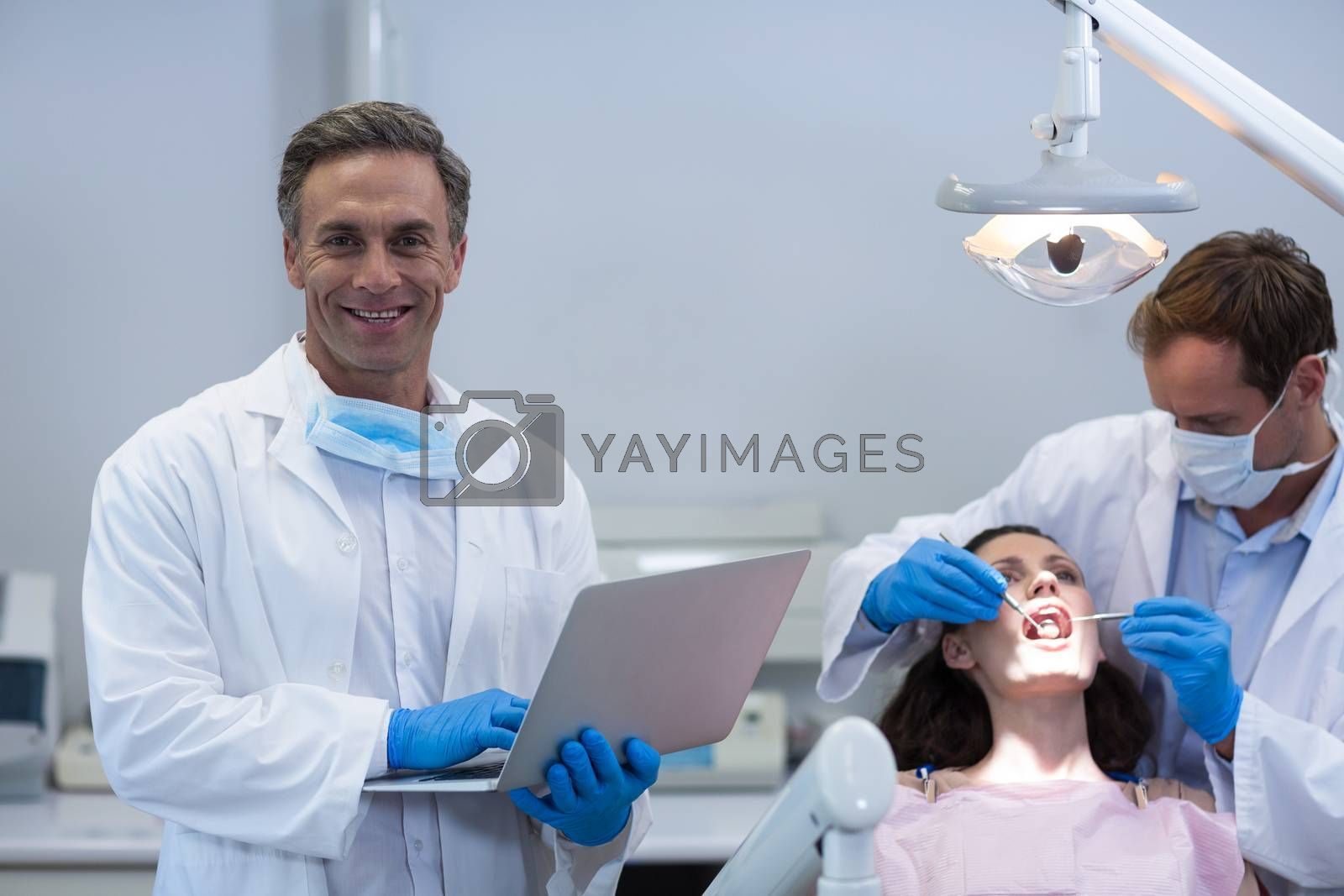 Portrait of dentist holding laptop while colleague examining a female patient at dental clinic