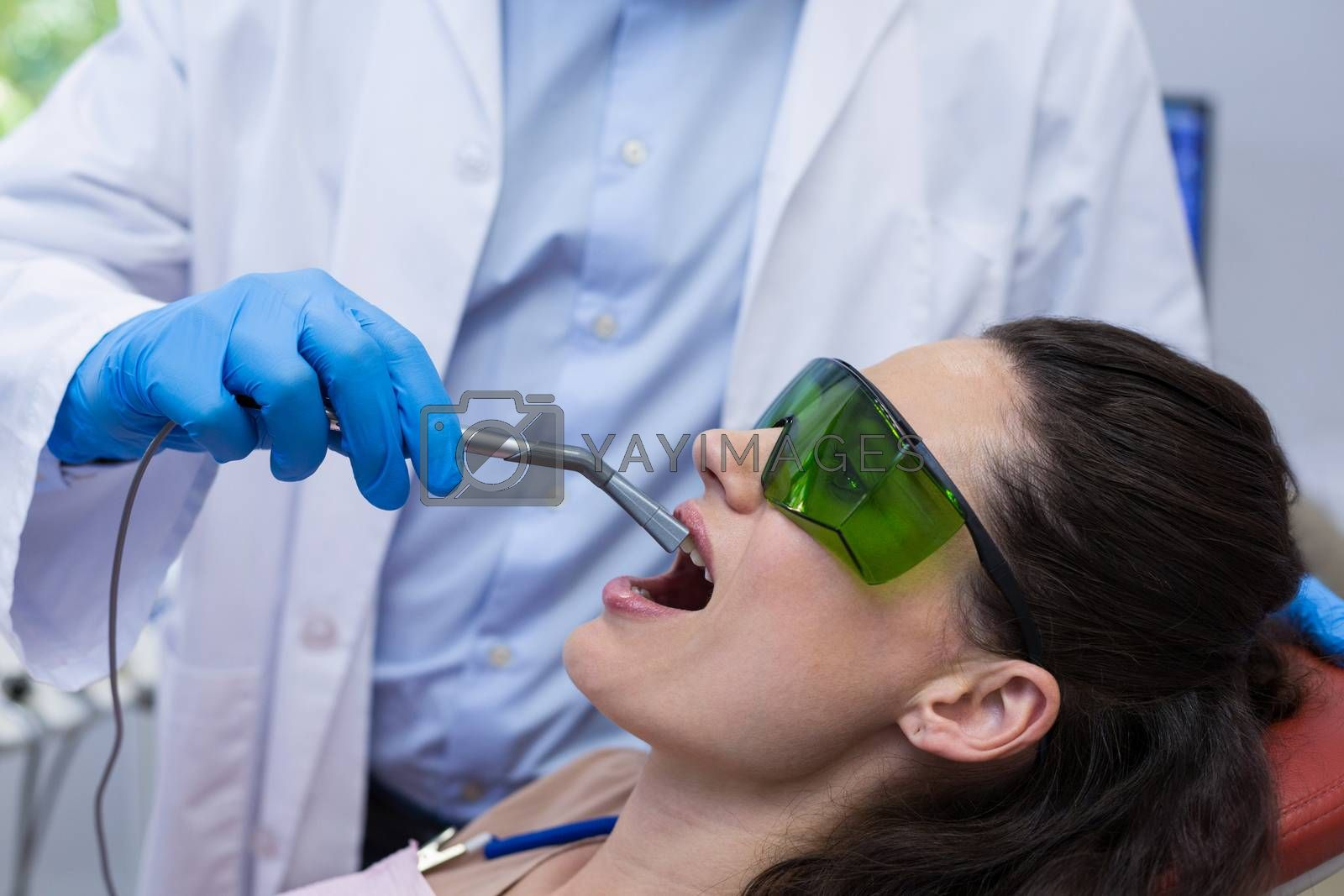 Dentist examining a female patient with dental equipment at dental clinic