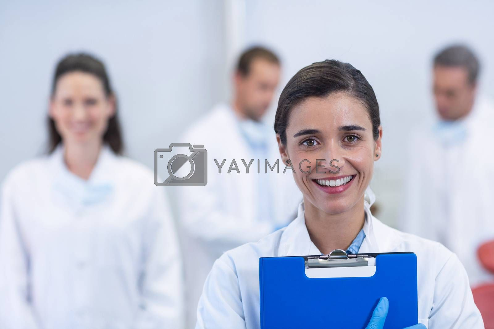 Portrait of smiling dentist standing at dental clinic