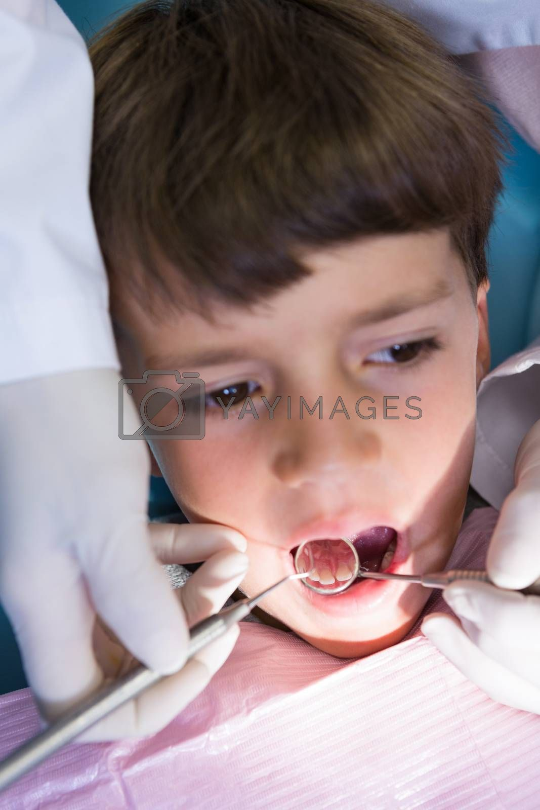 Close-up of boy looking away while receiving dental treatment at clinic