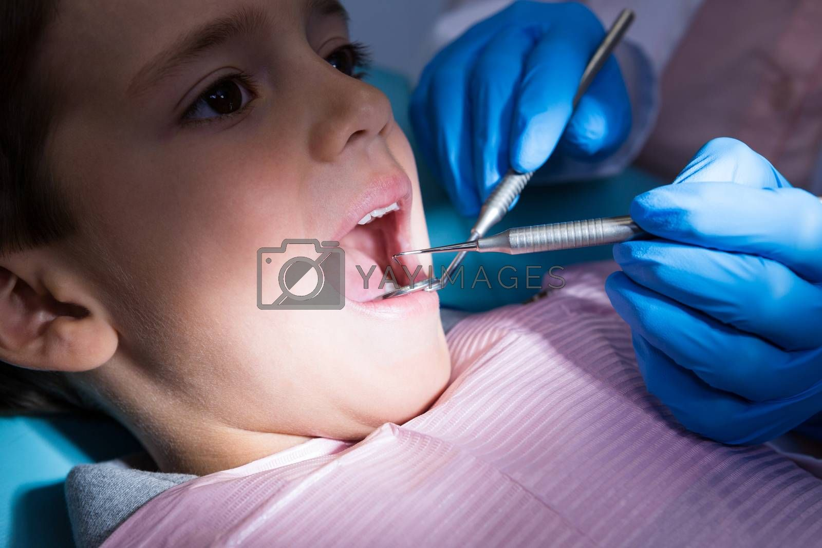 Close up of dentist giving dental treatment to boy at clinic