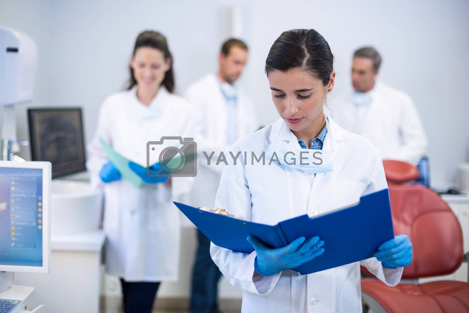Attentive dentist looking at reports in dental clinic