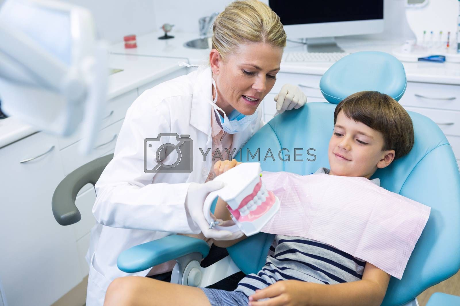 Dentist holding dental mould while talking with boy at clinic