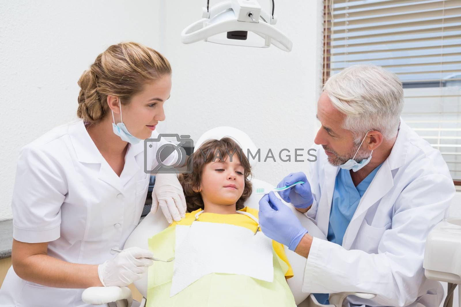 Pediatric dentist showing little boy how to brush his teeth at the dental clinic