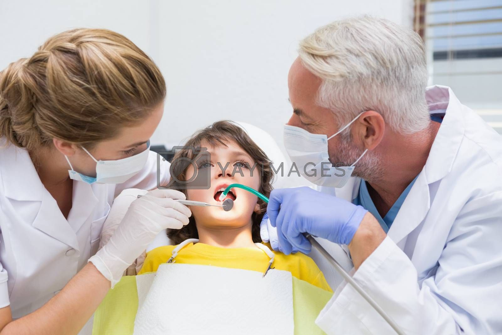 Pediatric dentist examining a little boys teeth with his assistant at the dental clinic