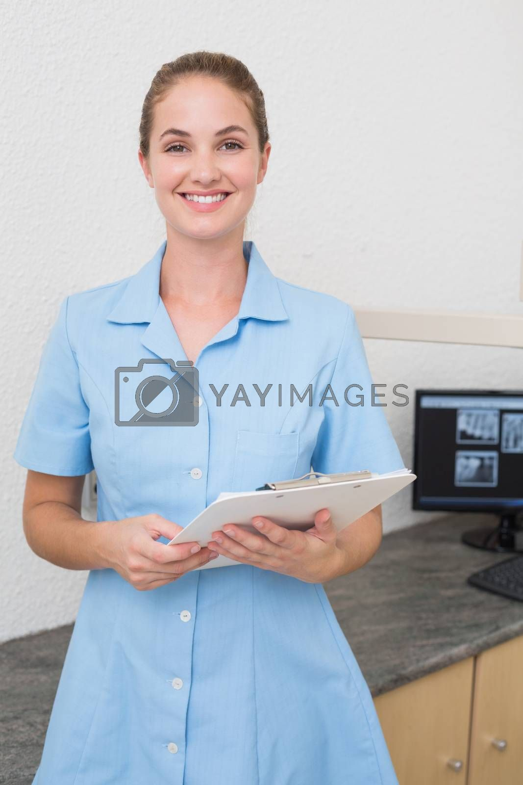 Smiling dental assistant looking at camera holding clipboard at the dental clinic