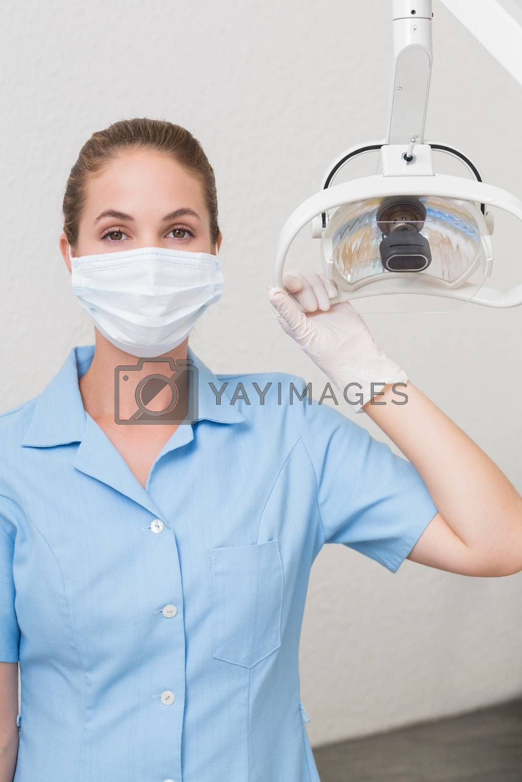 Dental assistant in mask holding light at the dental clinic