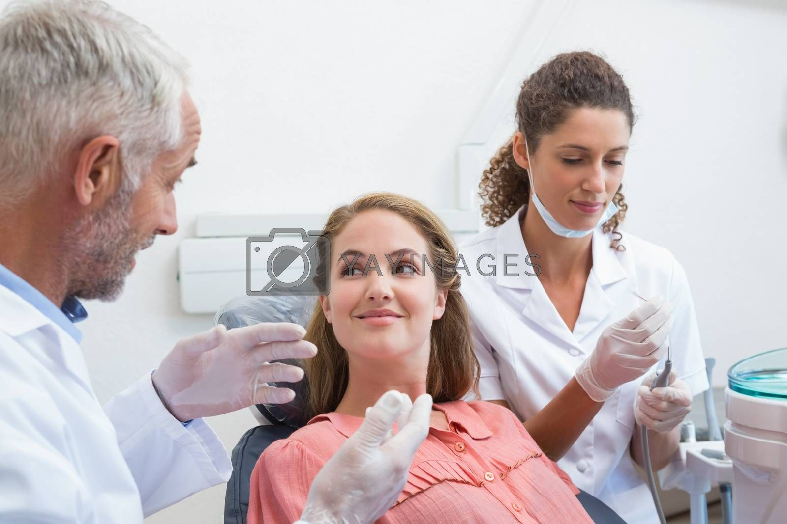Dentist talking with patient while nurse prepares the tools at the dental clinic