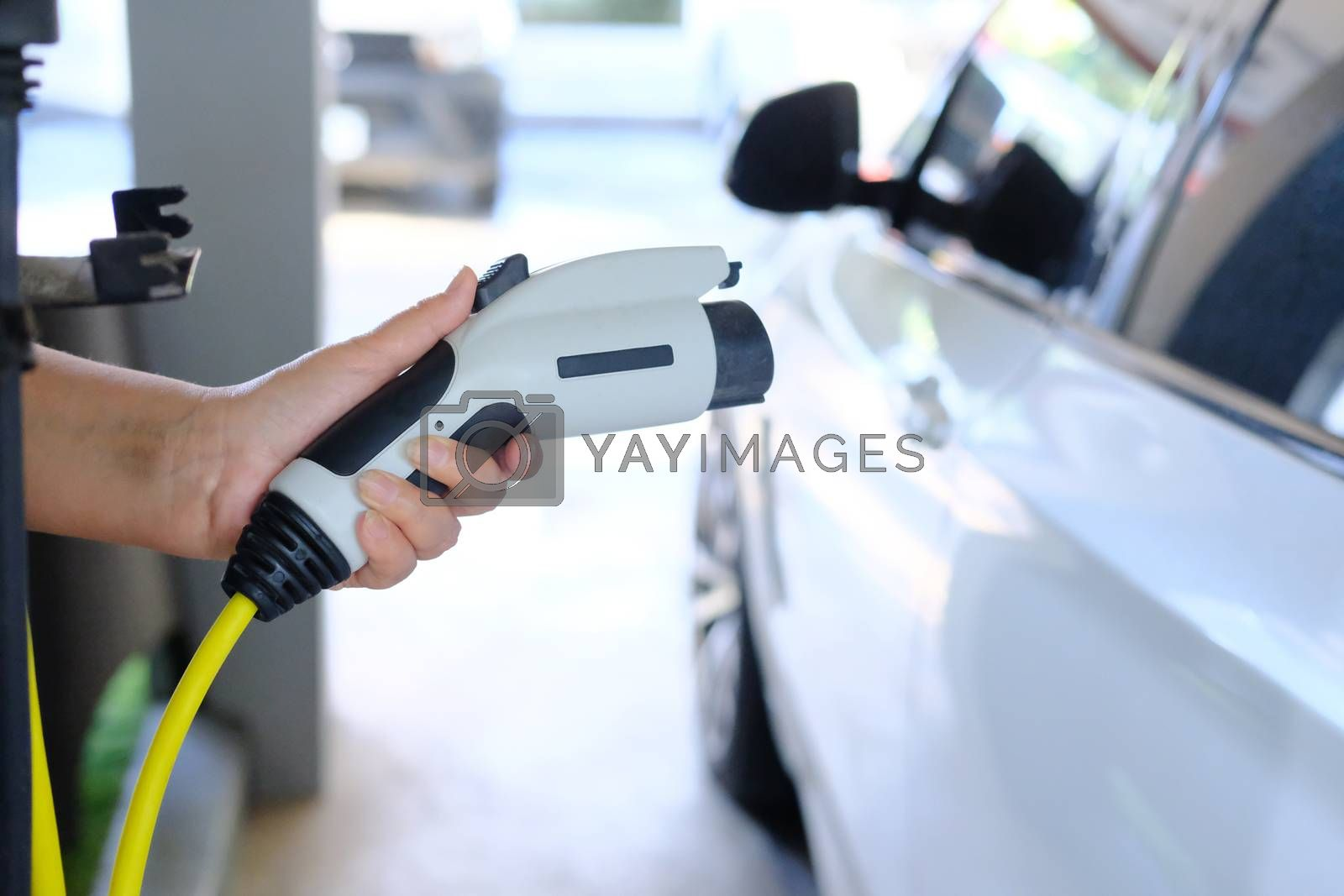 Close up of Human hand holding plug in connector for Charging electric car on electric car background. Concept of an electric car  ecological way of driving.