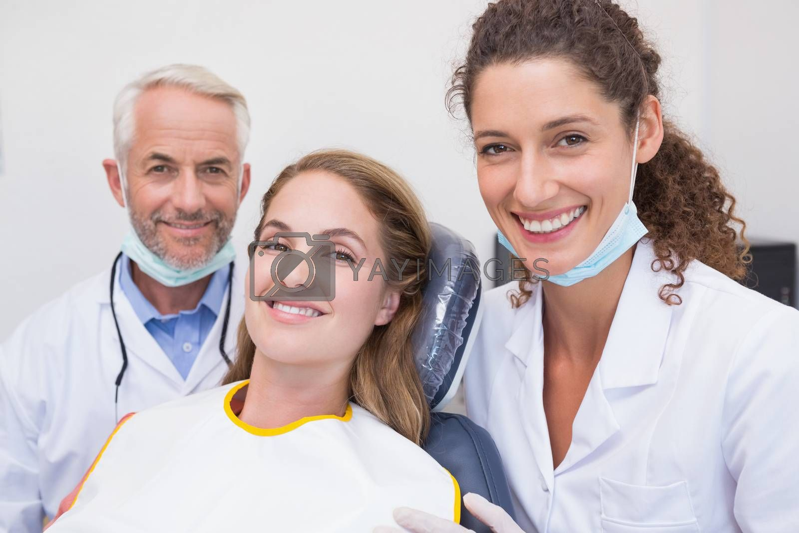 Dentist his assistant and patient all smiling at camera at the dental clinic