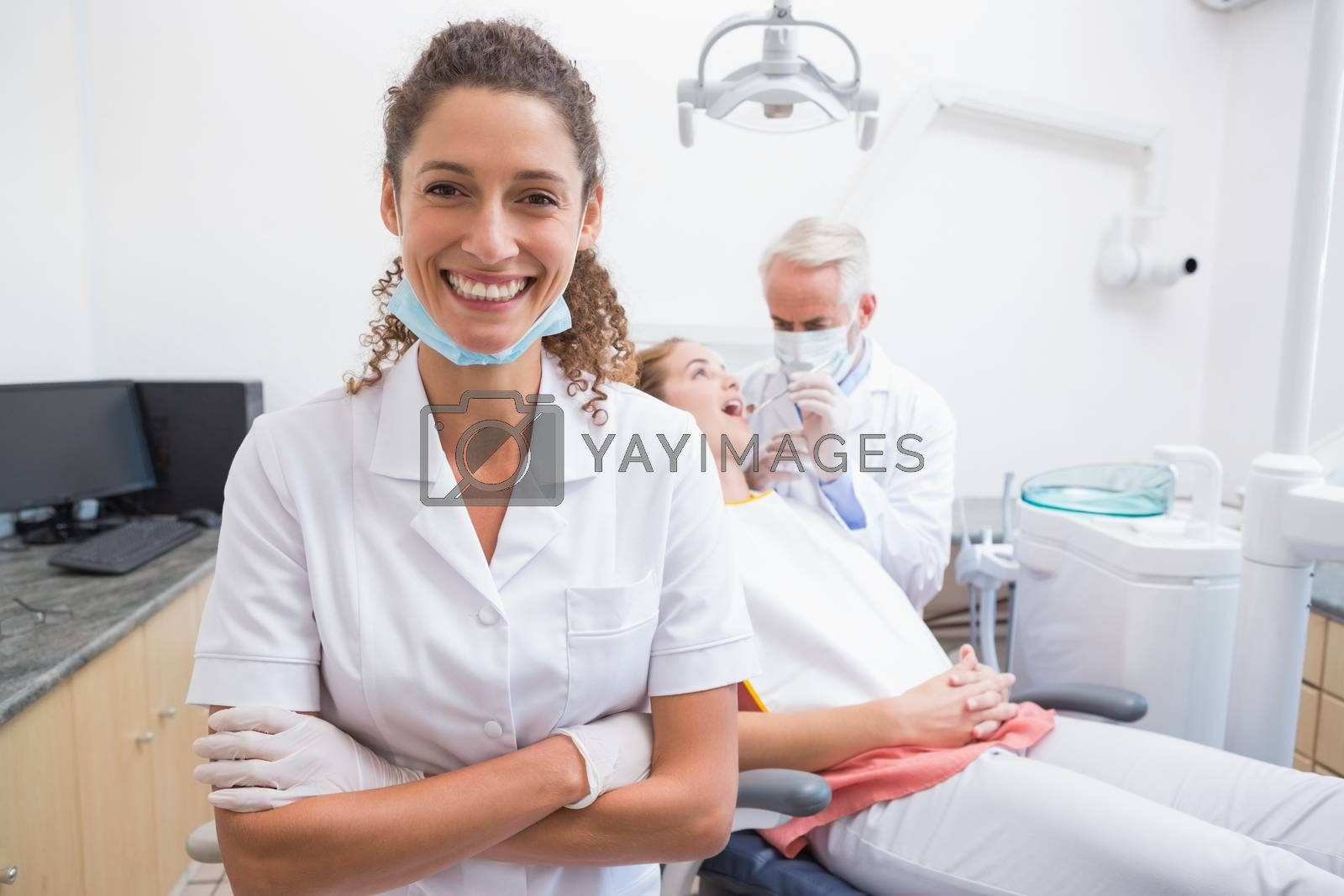 Dental assistant smiling at camera with dentist and patient behind at the dental clinic