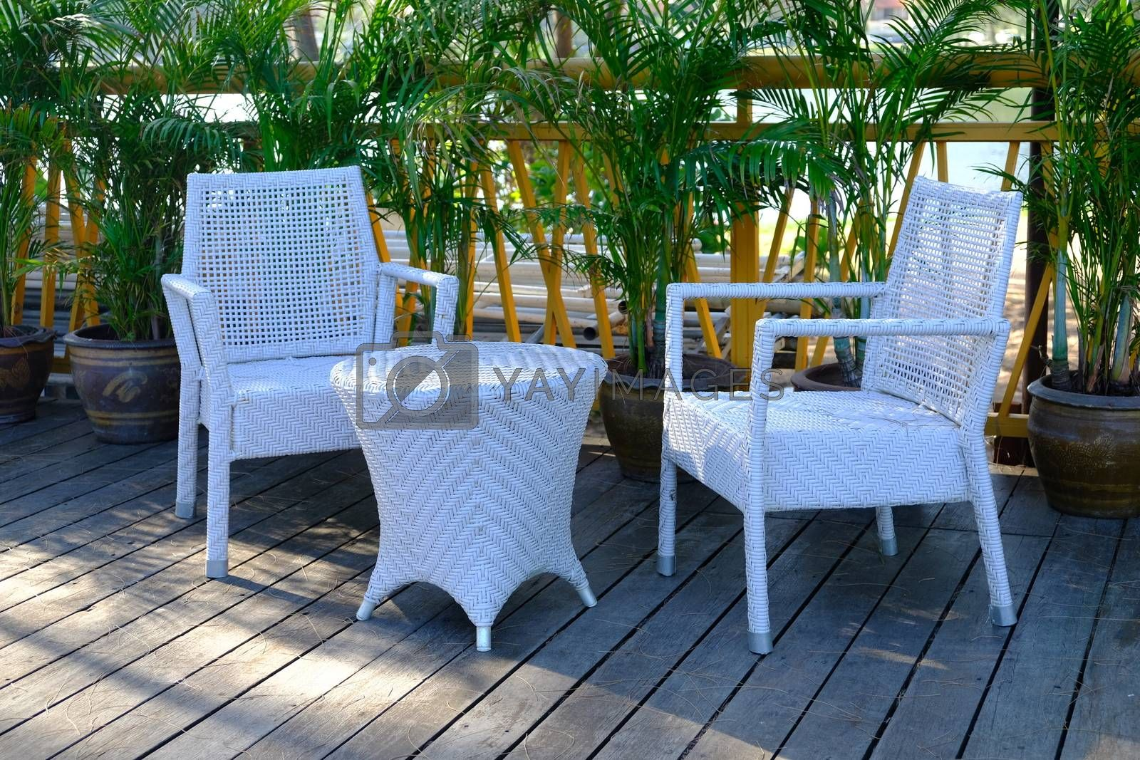 CloseUp of plastic weave chairs and table in outdoor terrace. Wicker weave outdoor Plastic furniture white color.