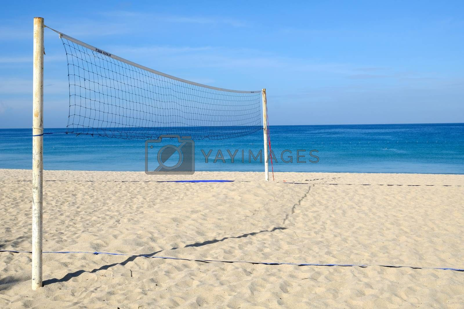 Closeup of Volleyball net on the tropical beach with blue sky. Sunny day on an empty beach.