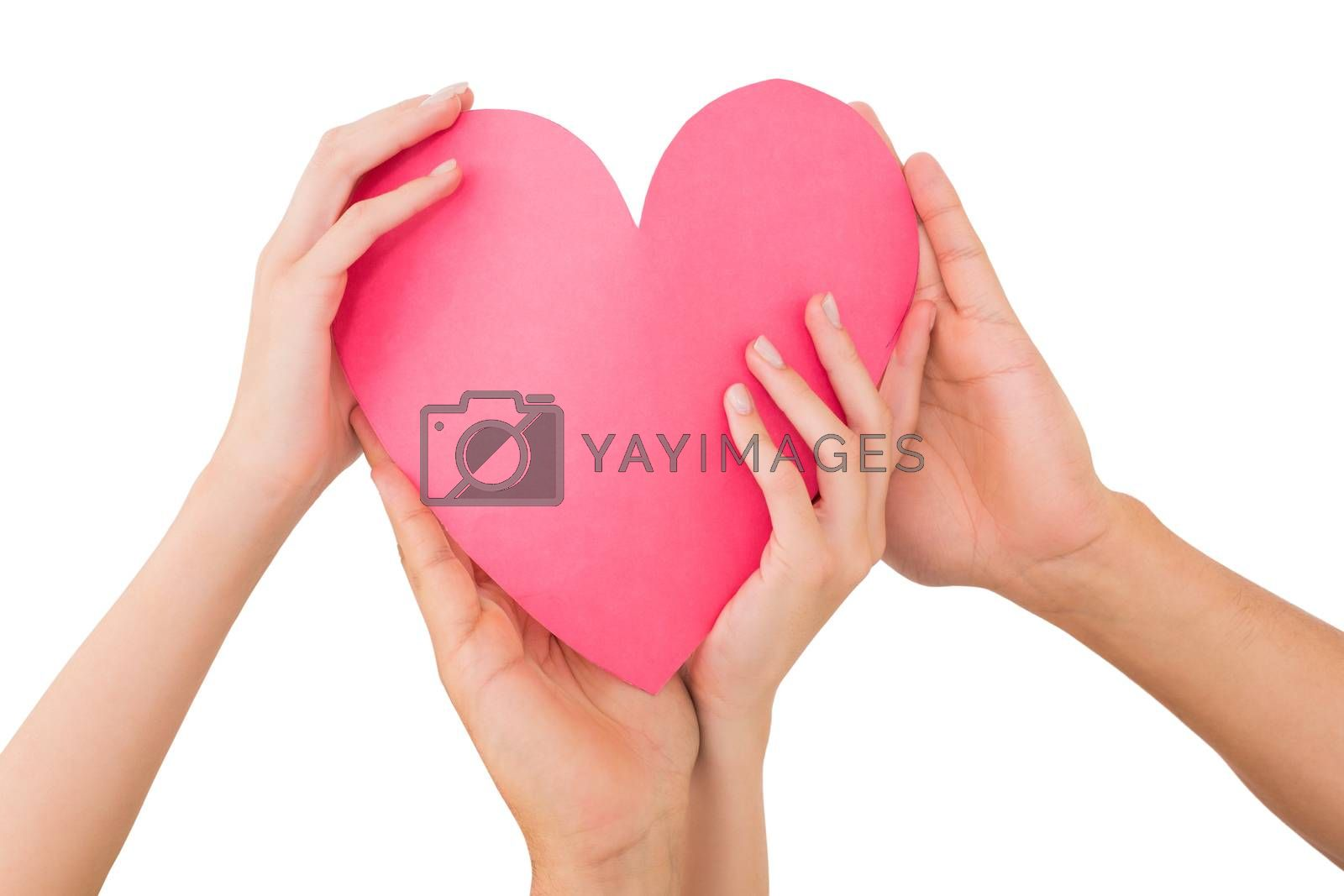 Couple holding a paper heart on white background