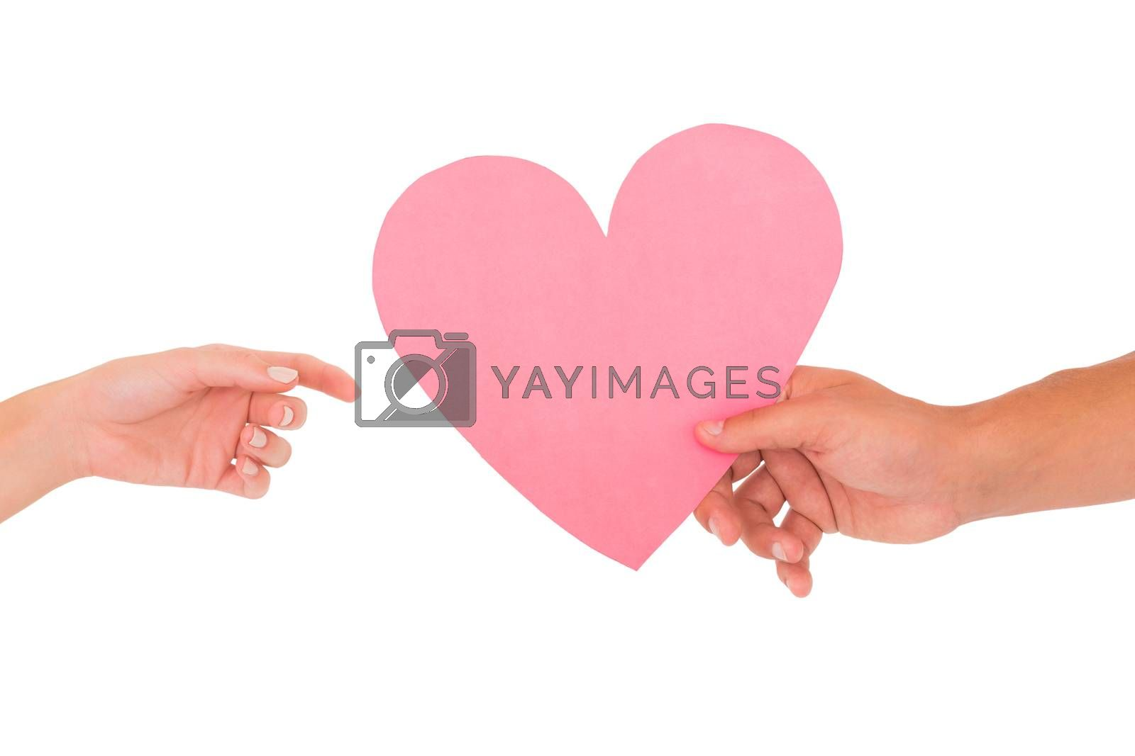 Couple passing a paper heart on white background