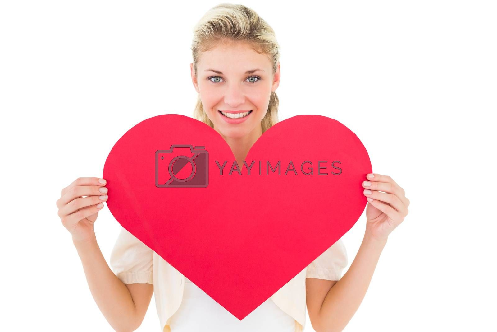 Attractive young blonde showing red heart on white background