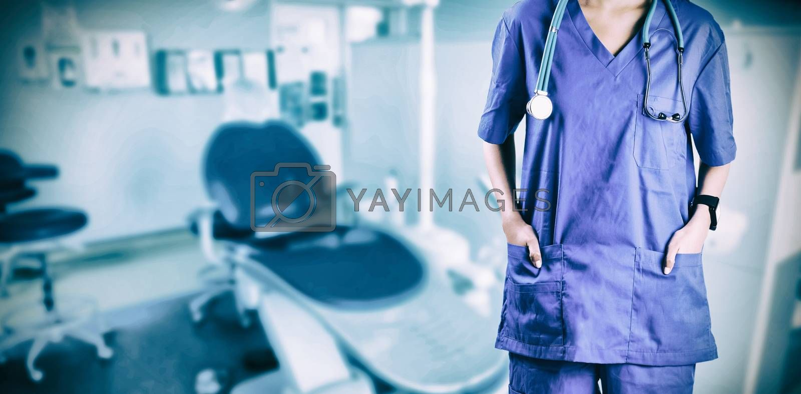Asian nurse with hands in pocket against high angle view of dental equipment