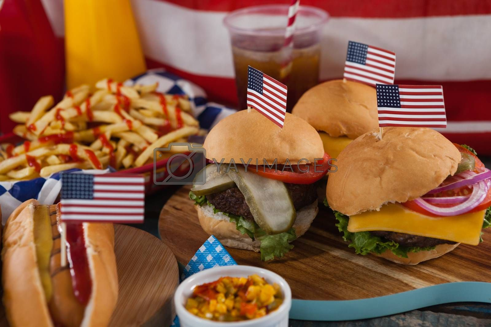 Hot dog and hamburgers decorated with 4th july theme on wooden board