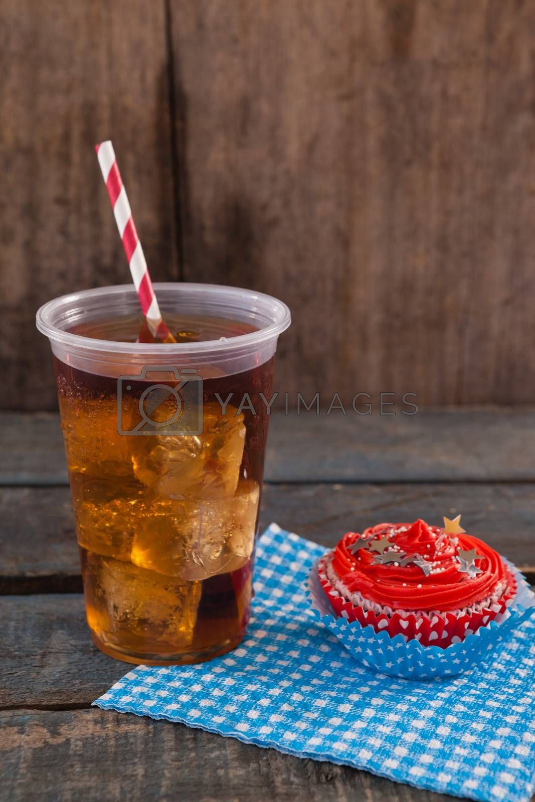 Royalty free image of Decorated cupcake and cold drink with 4th july theme by Wavebreakmedia