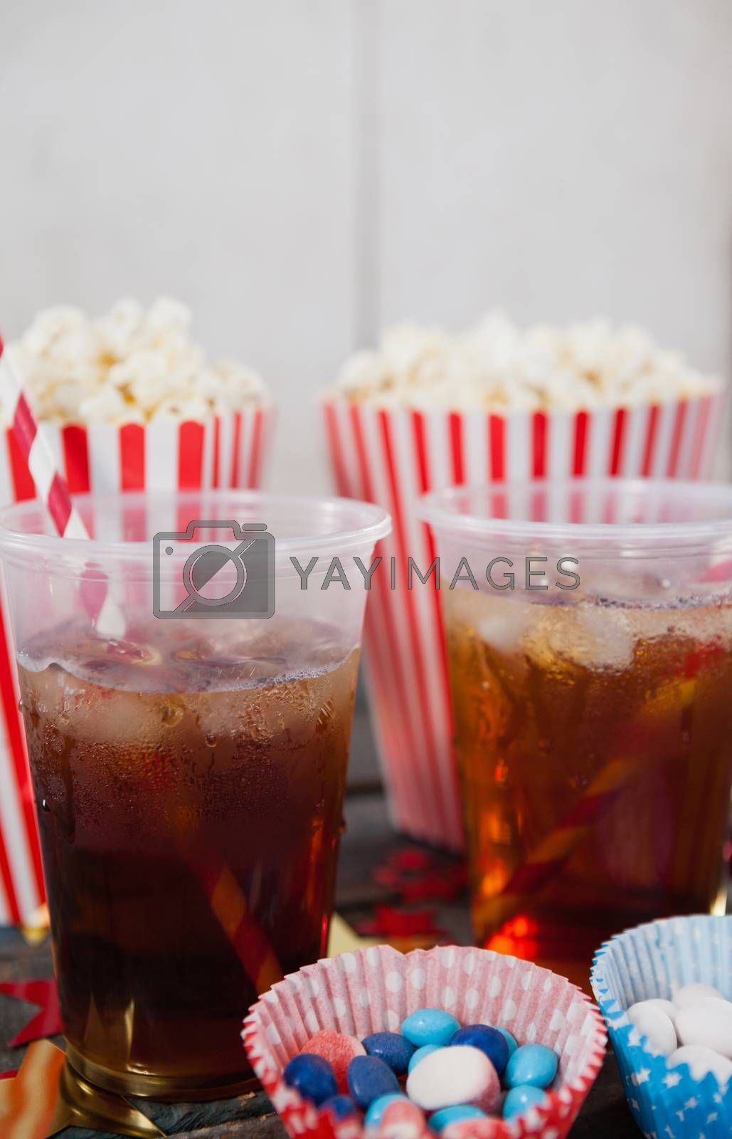 Close-up of popcorn, confectionery and drink with 4th july theme