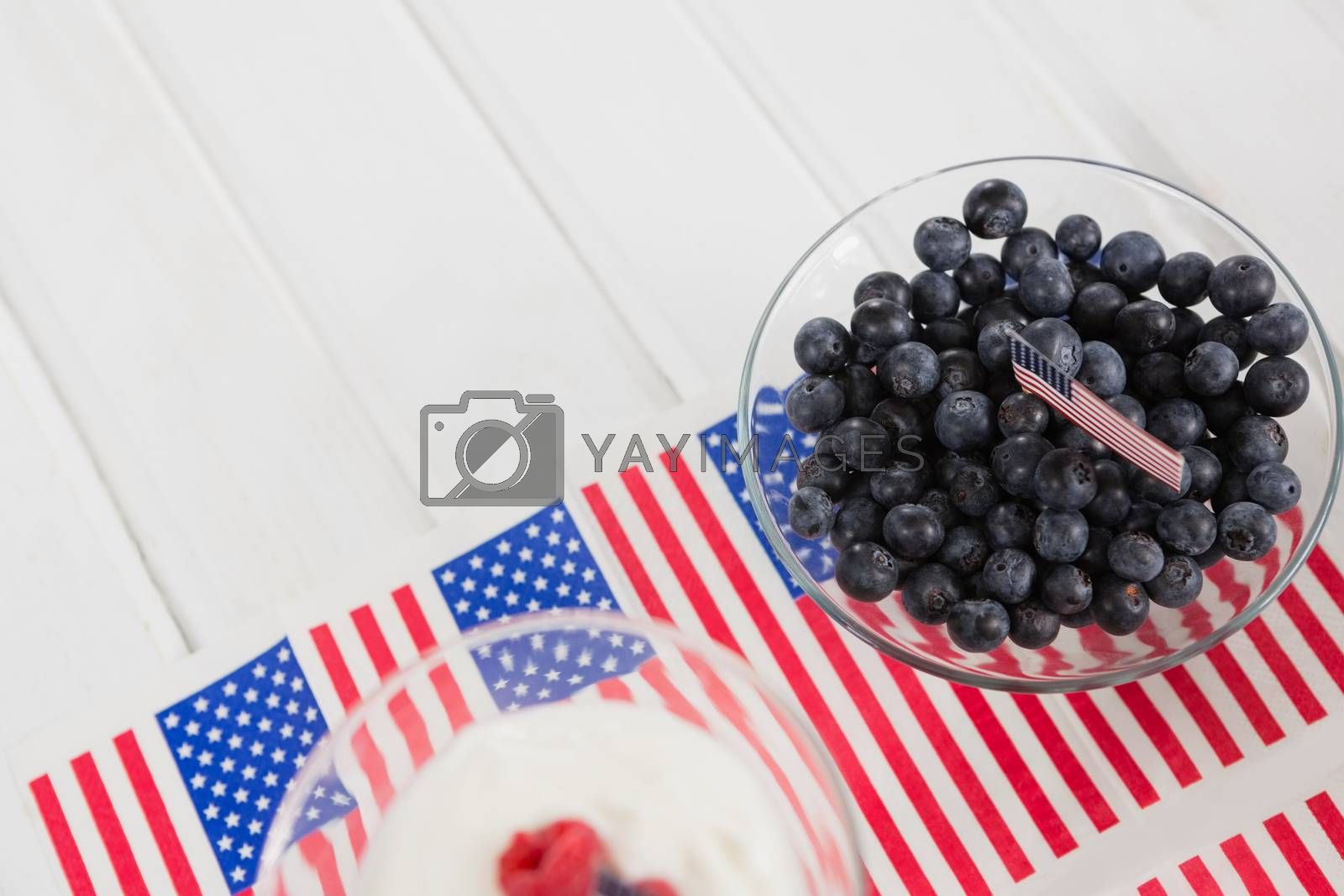 Black berries in bowl with 4th july theme on wooden table