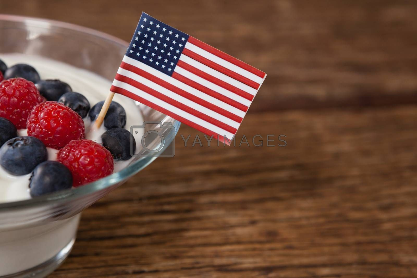 Close-up of fruit ice cream decorated with 4th july theme on wooden table