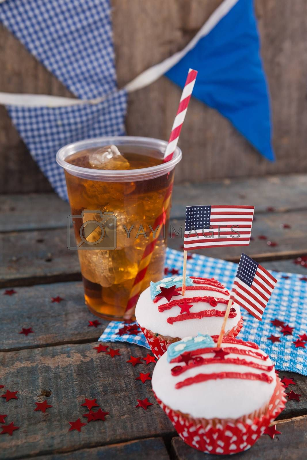 Decorated cupcakes and cold drink with 4th july theme by Wavebreakmedia