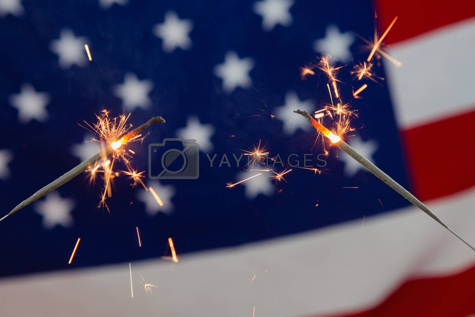 Close-up of sparklers burning against American flag background