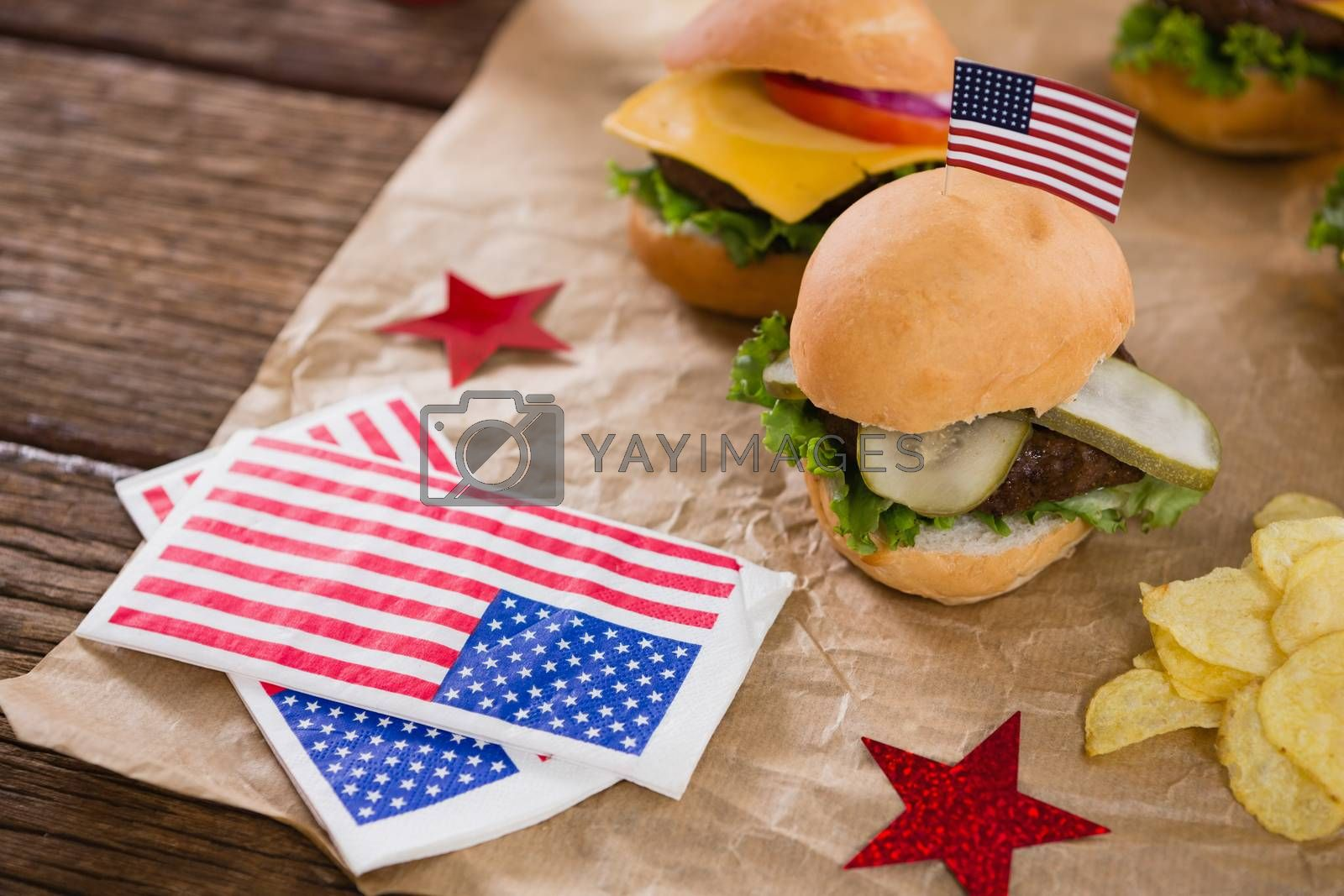 Burger and potato chips decorated with 4th july theme on wooden table