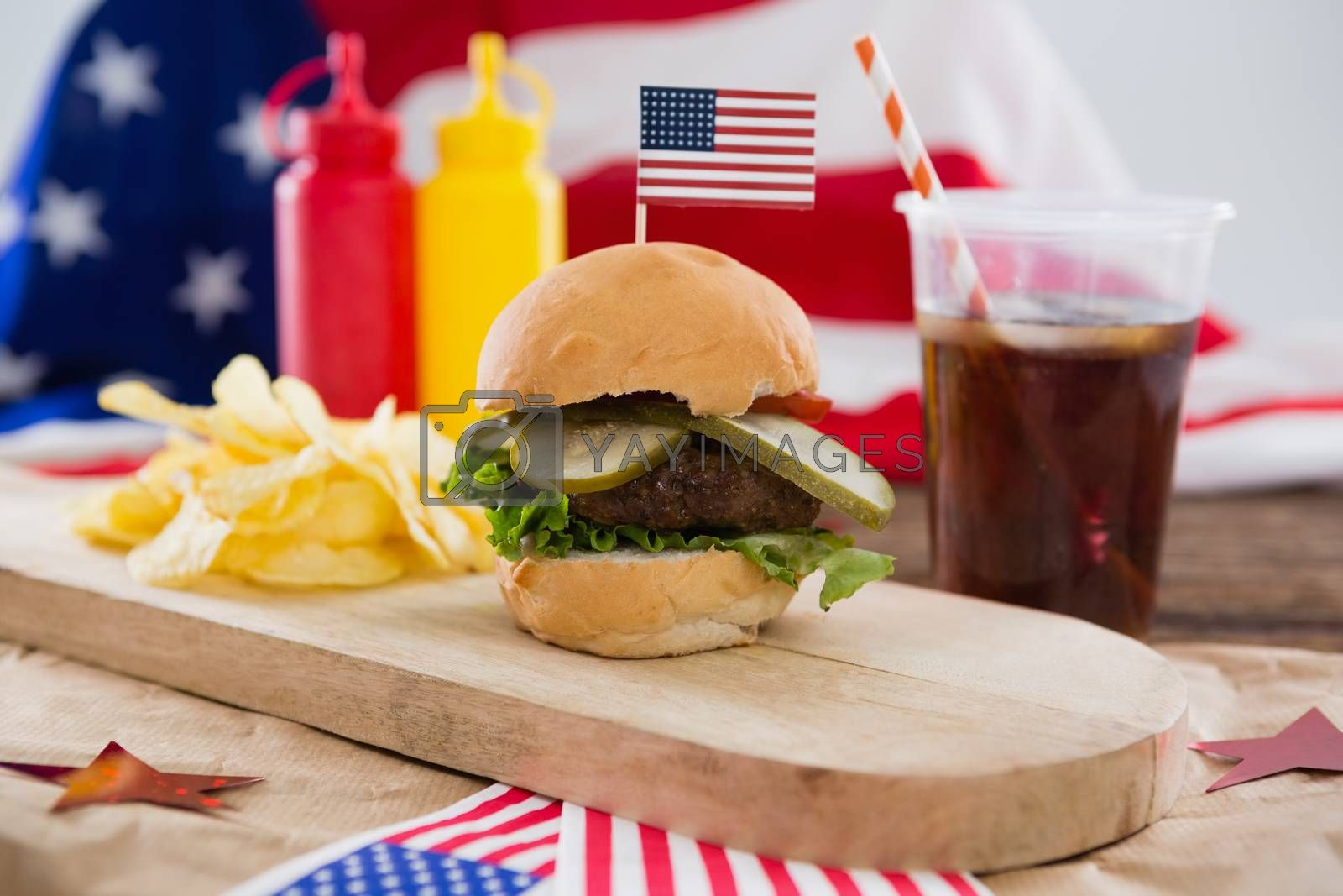 Food and cold drink decorated with 4th july theme on wooden table
