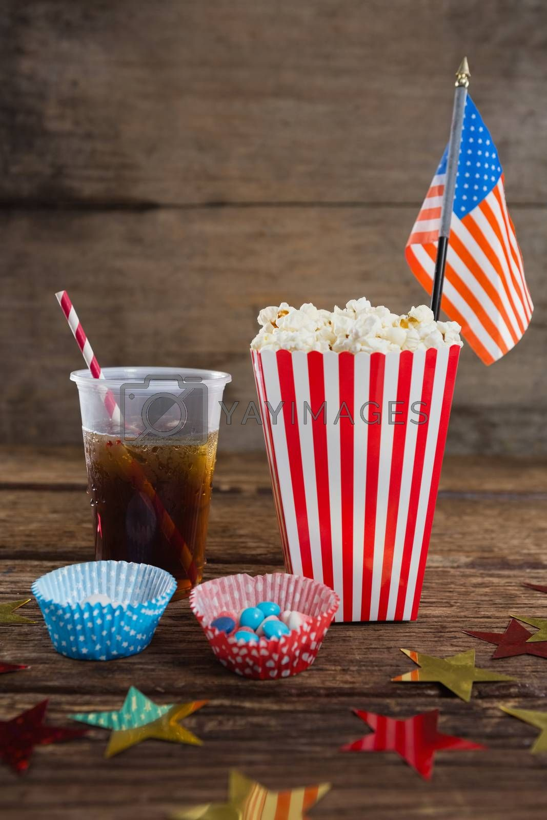Royalty free image of Popcorn, sweet food and cold drink decorated with 4th july theme by Wavebreakmedia