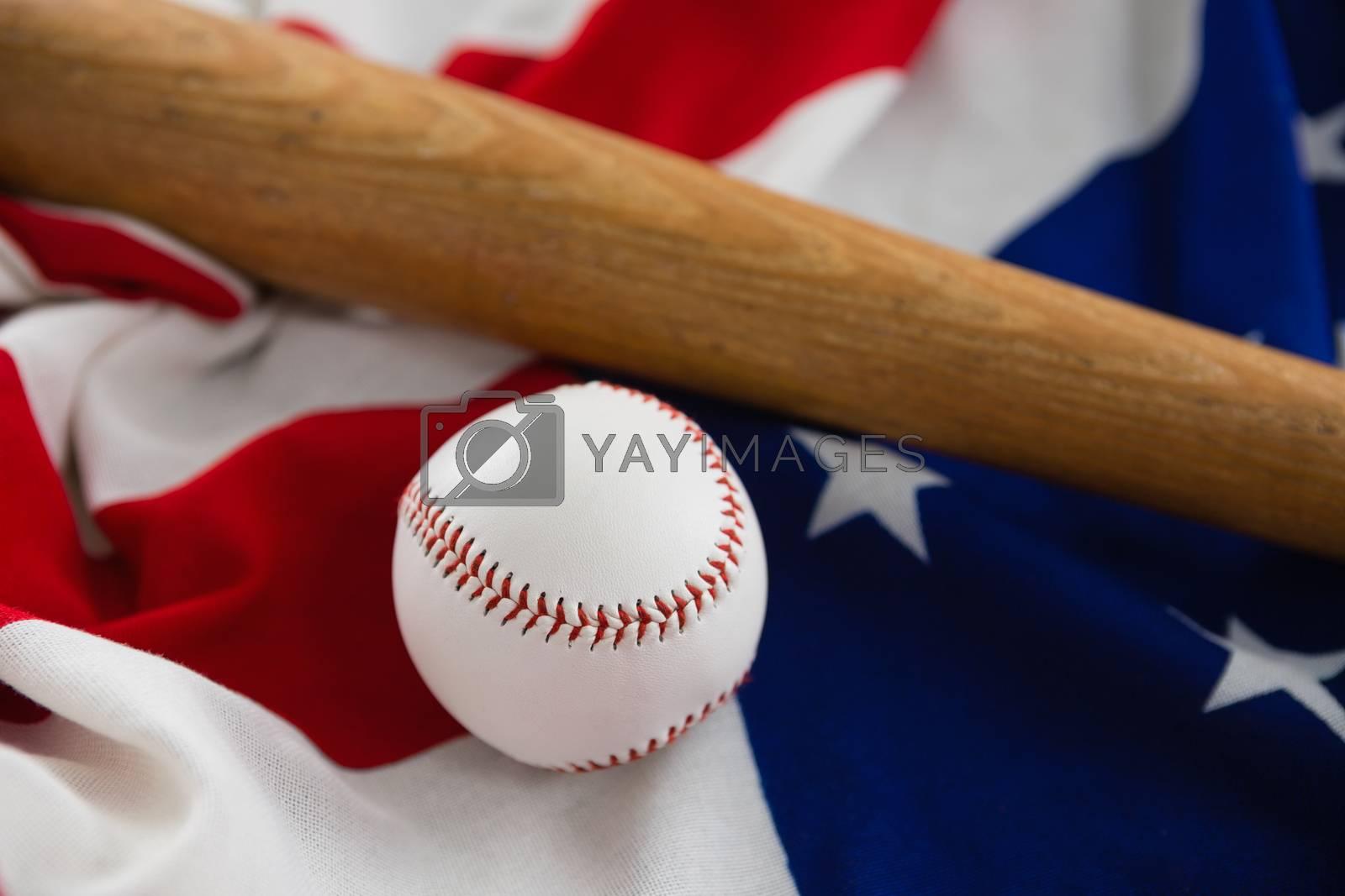 Close-up of baseball bat and ball on American flag