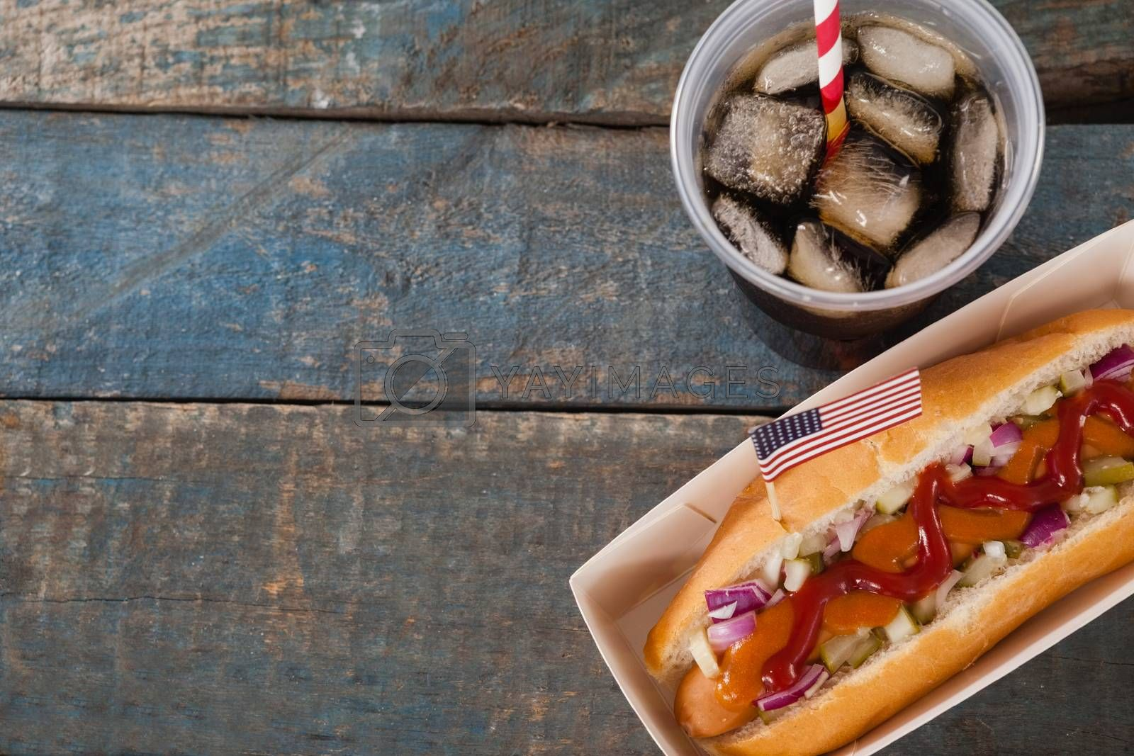 Hot dog and cold drink on with 4th july theme on wooden table