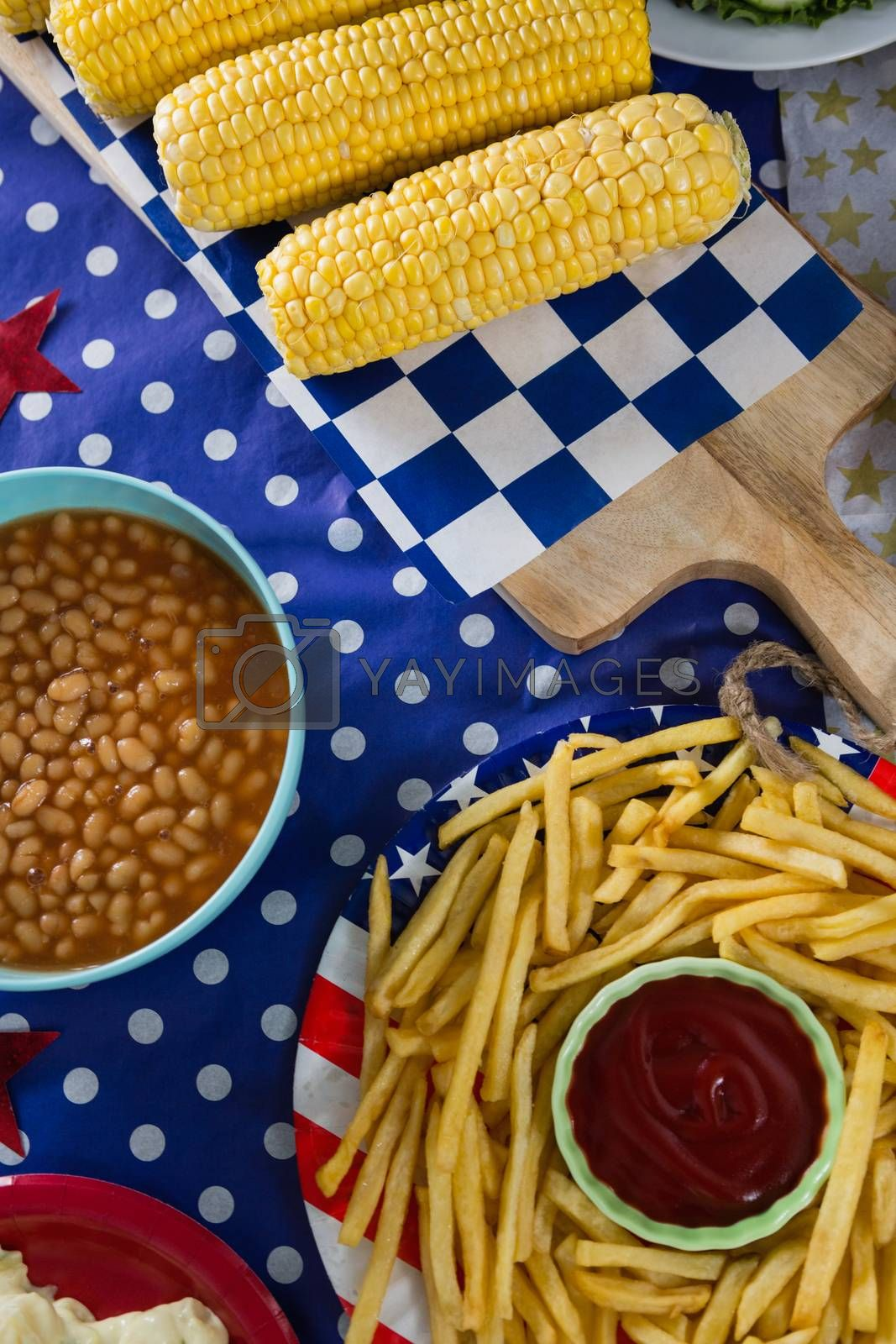 Royalty free image of French fries and corn cob on wooden table with 4th july theme by Wavebreakmedia