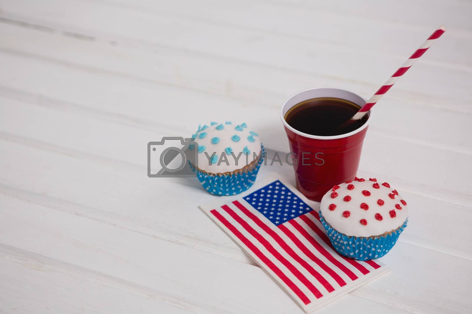Decorated cupcakes and cold drink with 4th july theme on wooden table